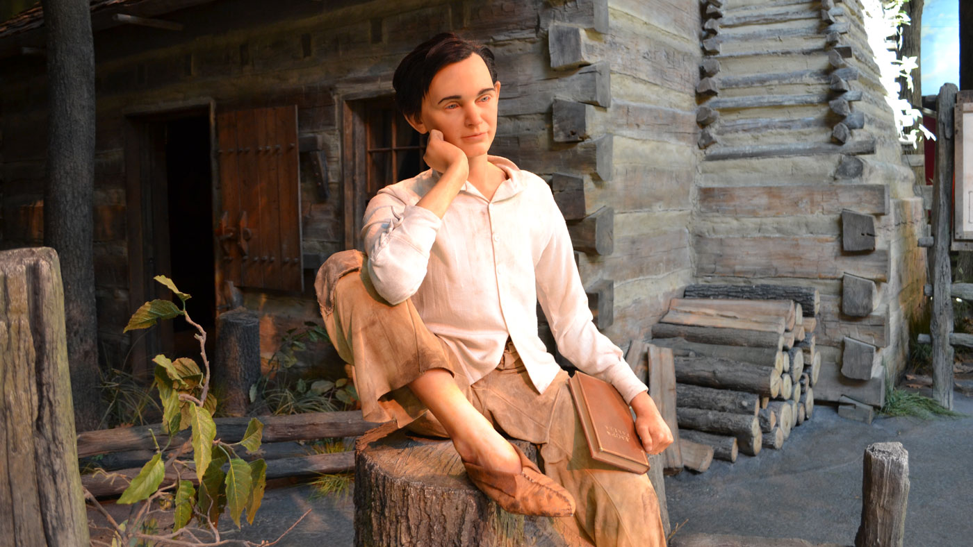 young Abraham Lincoln is depicted outside his boyhood log cabin at the Abraham Lincoln Presidential Library and Museum