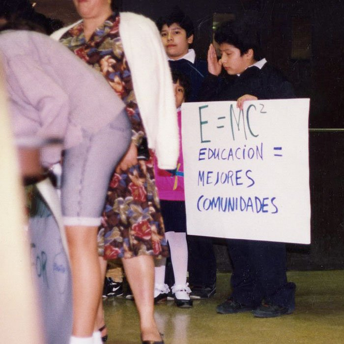 A young child holds a sign in protest.