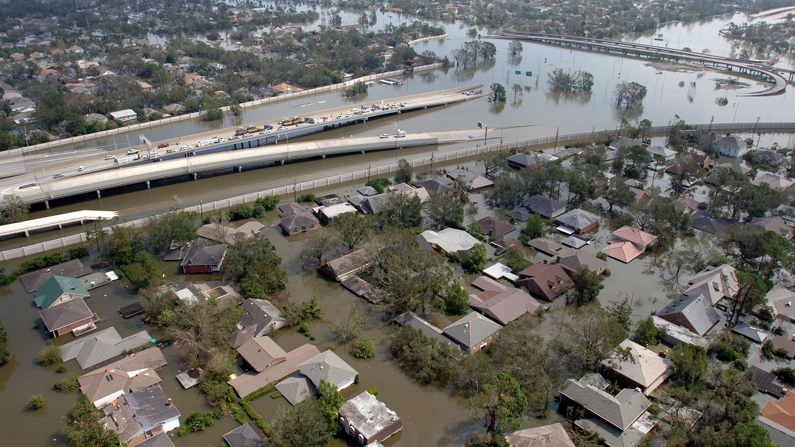 A flooded New Orleans neighborhood with a roadway going down into flood waters after Hurricane Katrina on August 29, 2005