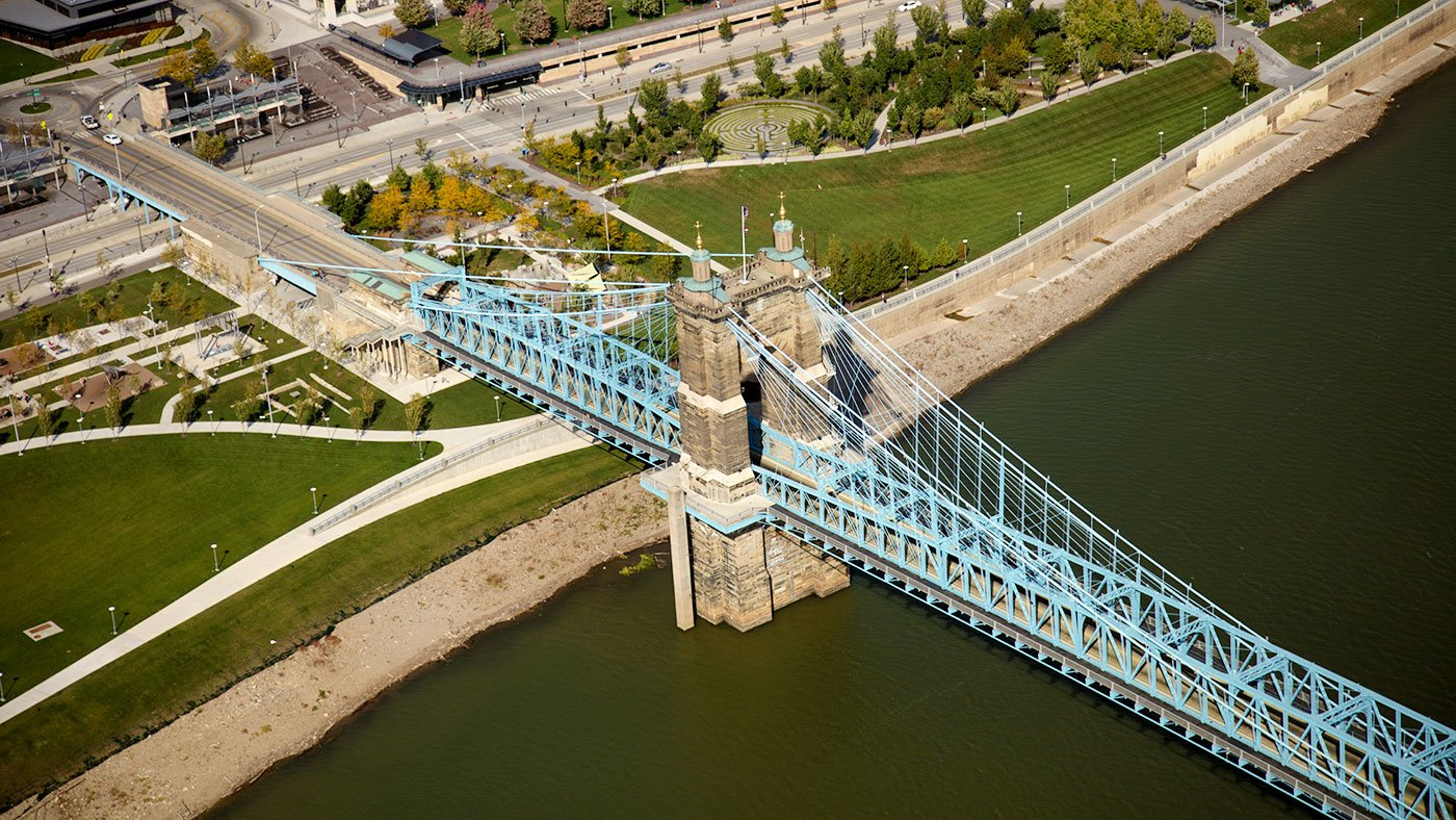 Aerial view of downtown Cincinnati, Ohio, focusing on the 1867 John A. Roebling Suspension Bridge over the Ohio River