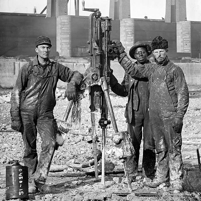 Laborers pose next to a compressed-air rock drill during the construction of the Chicago Sanitary and Ship Canal