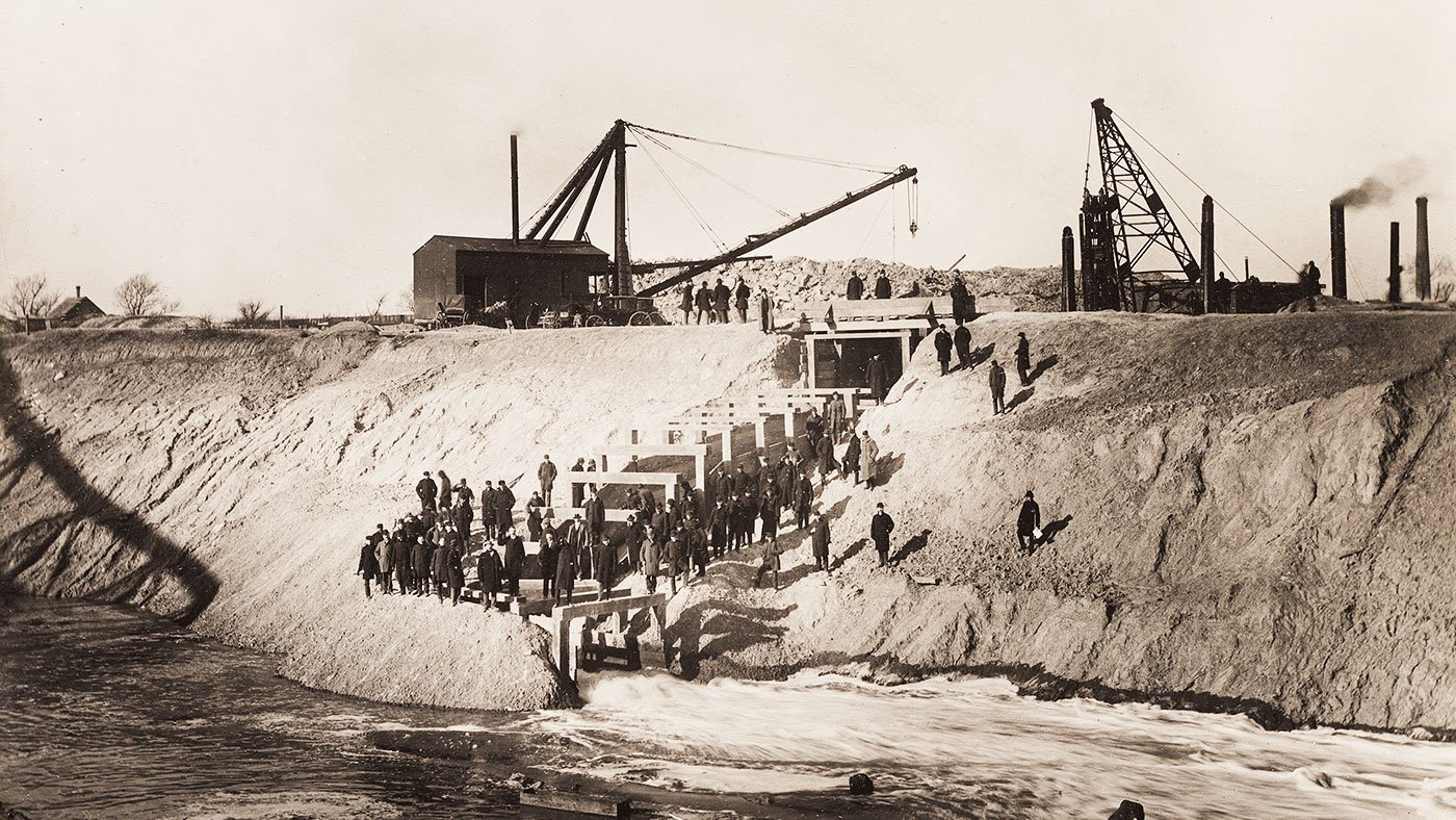 Sanitary District trustees and others pose for a photo after breaking the last dam holding the Chicago River back from the Sanitary and Ship Canal on the morning of January 2, 1900