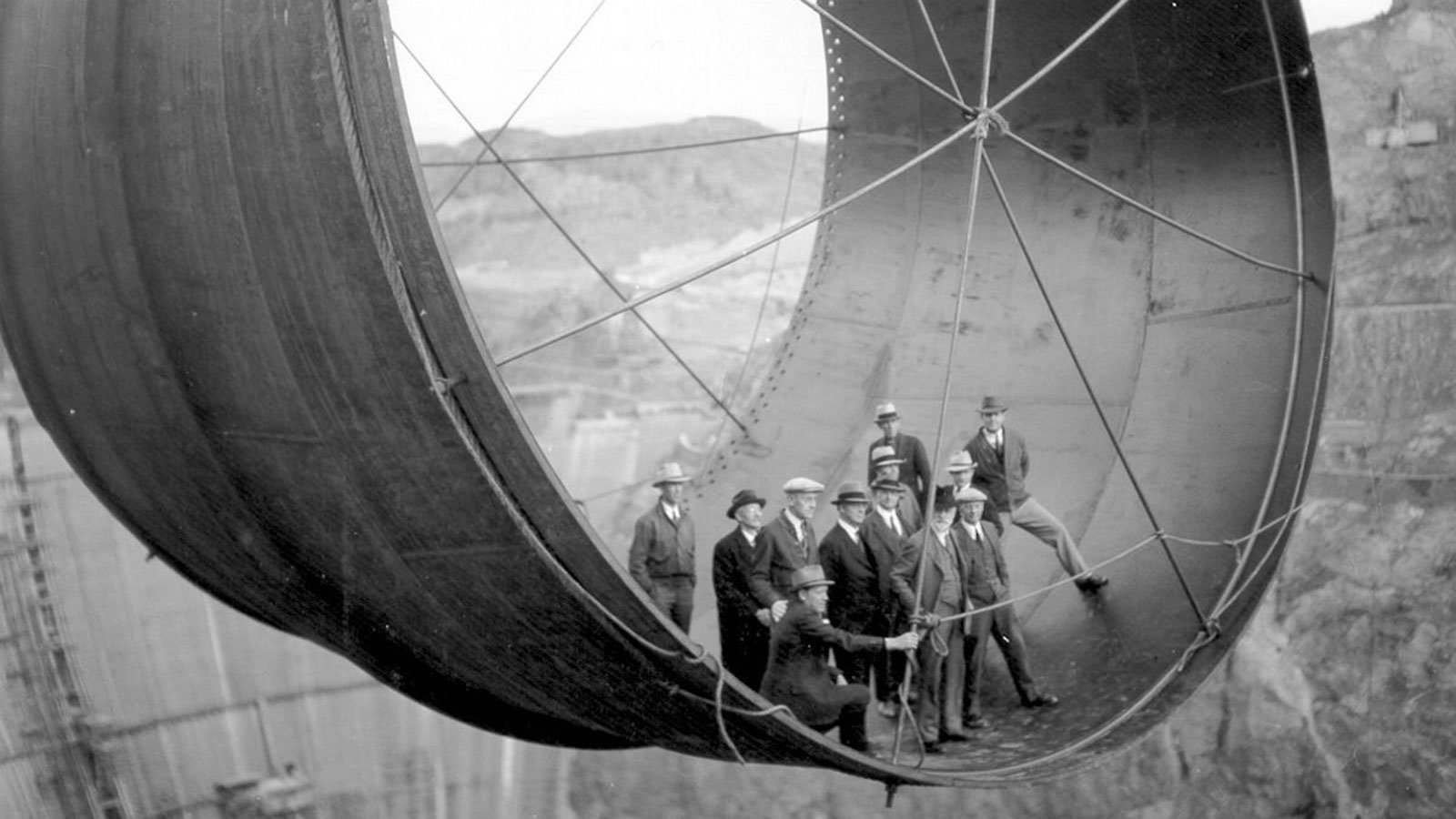 Officials ride in one of the penstock pipes of the soon-to-be-completed Hoover Dam