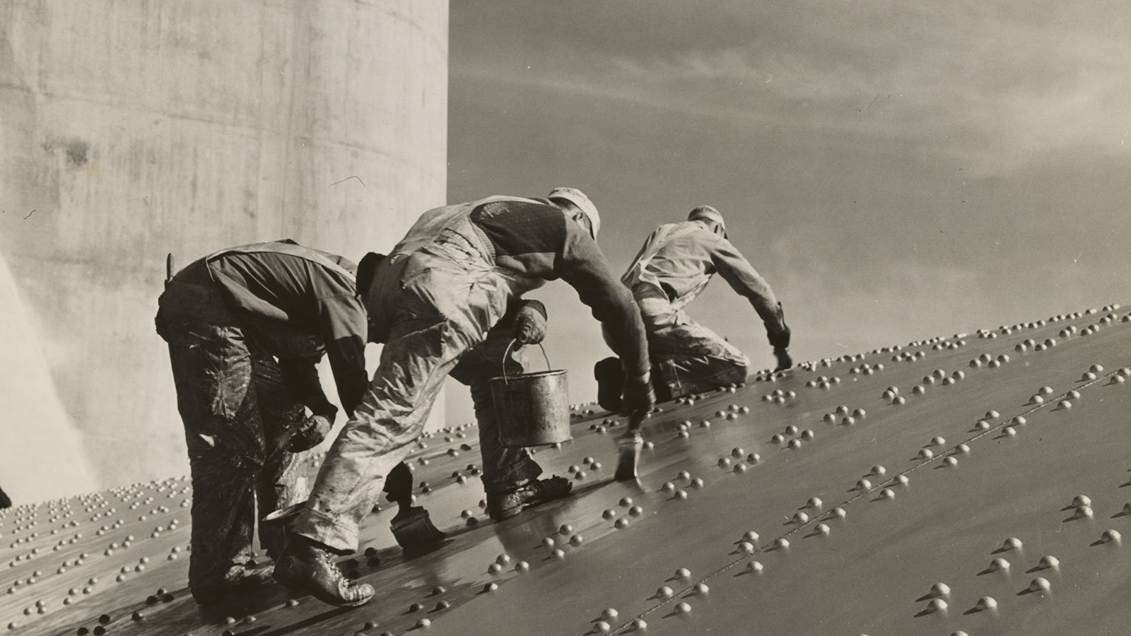 Three construction workers putting a coat of paint on a slanted wall of riveted-steel plates on the Hoover Dam spillway