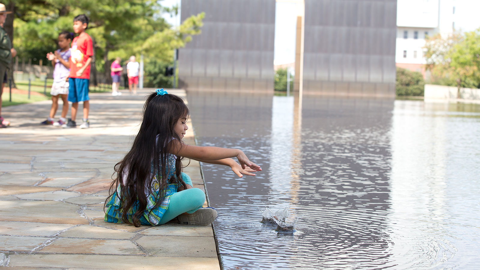 A girl plays in the reflecting pool at the Oklahoma City National Memorial