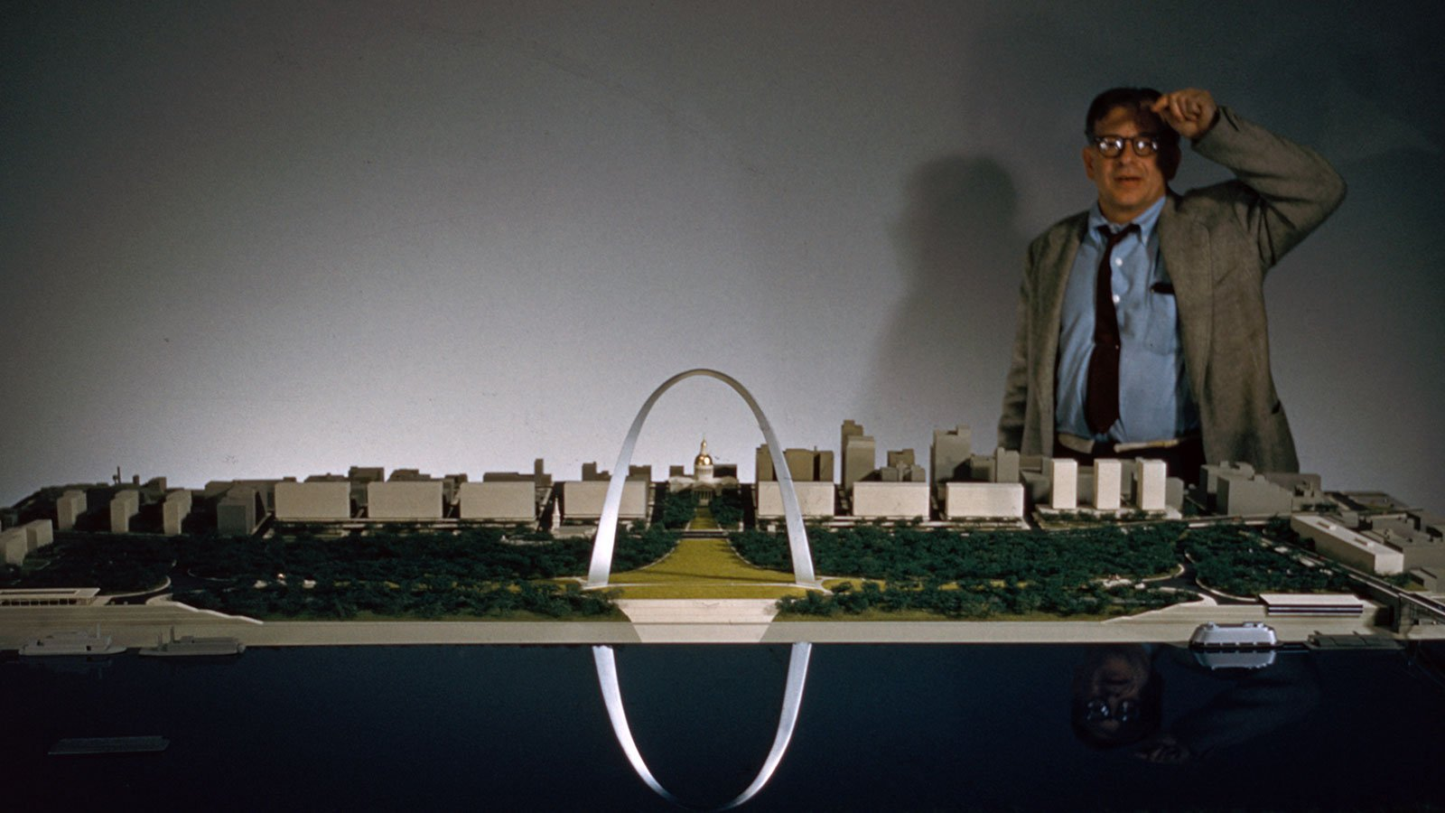 Eero Saarinen stands behind a model of the Saint Louis Gateway Arch in 1968