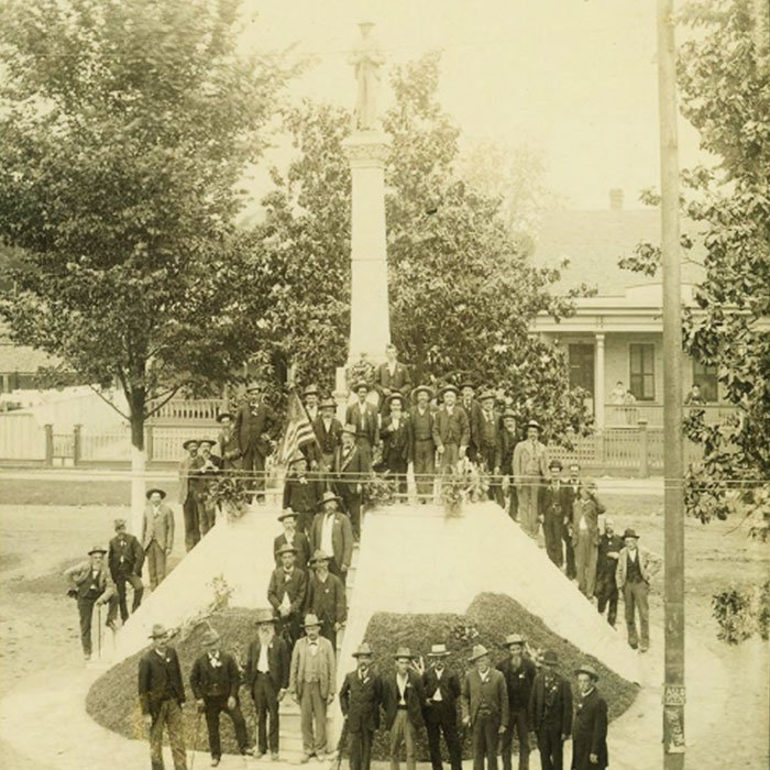 Confederate soldiers pose with a Confederate monument