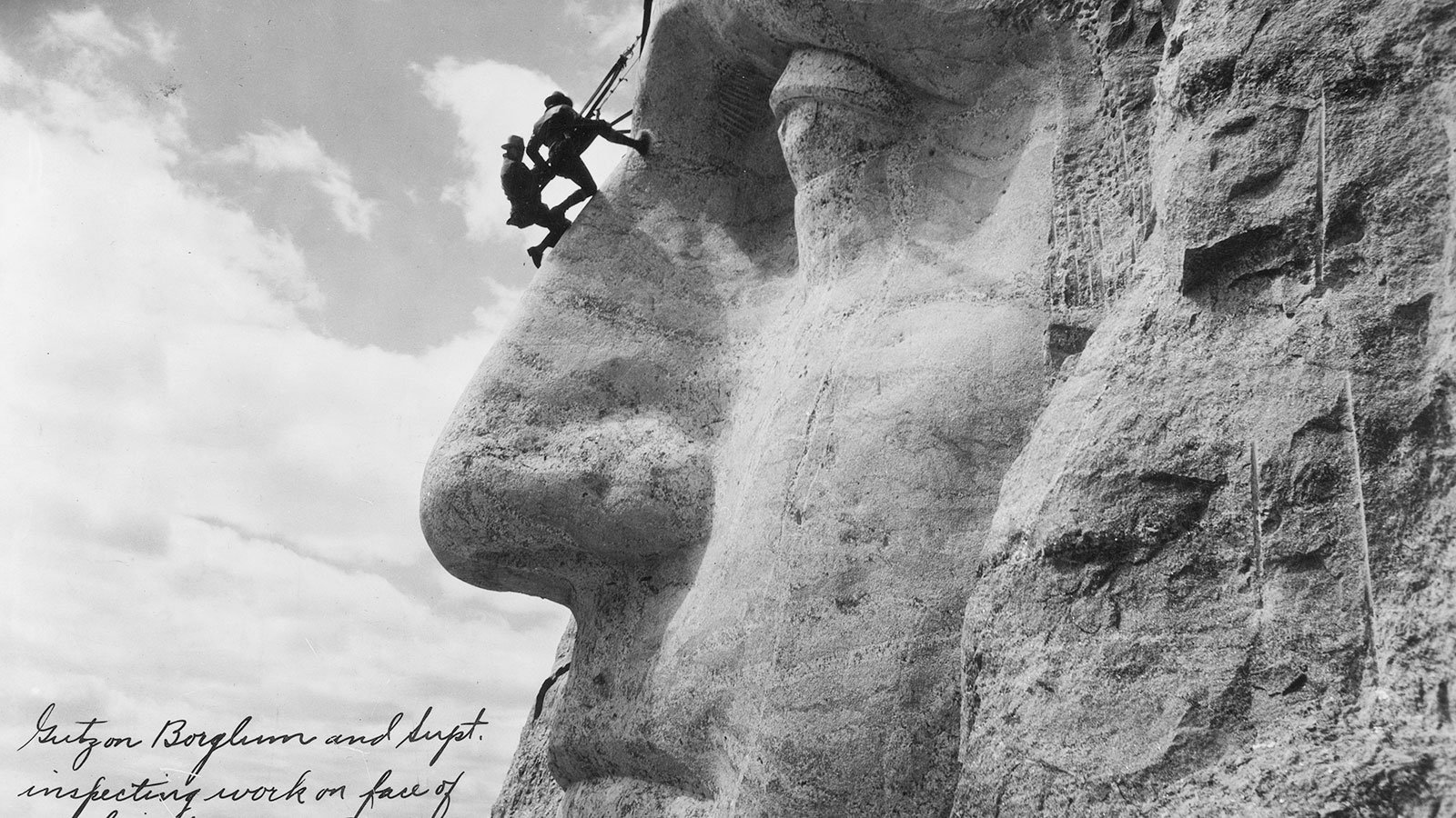 Gutzon Borglum and a superintendent inspecting work on the face of George Washington on Mount Rushmore