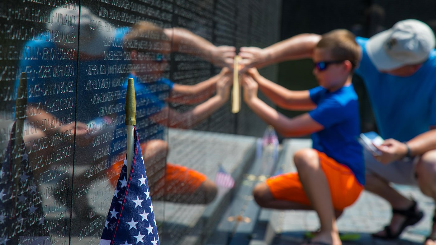 Two visitors make a rubbing of a name of a dead or missing soldier at the Vietnam Veterans Memorial in Washington, D.C.