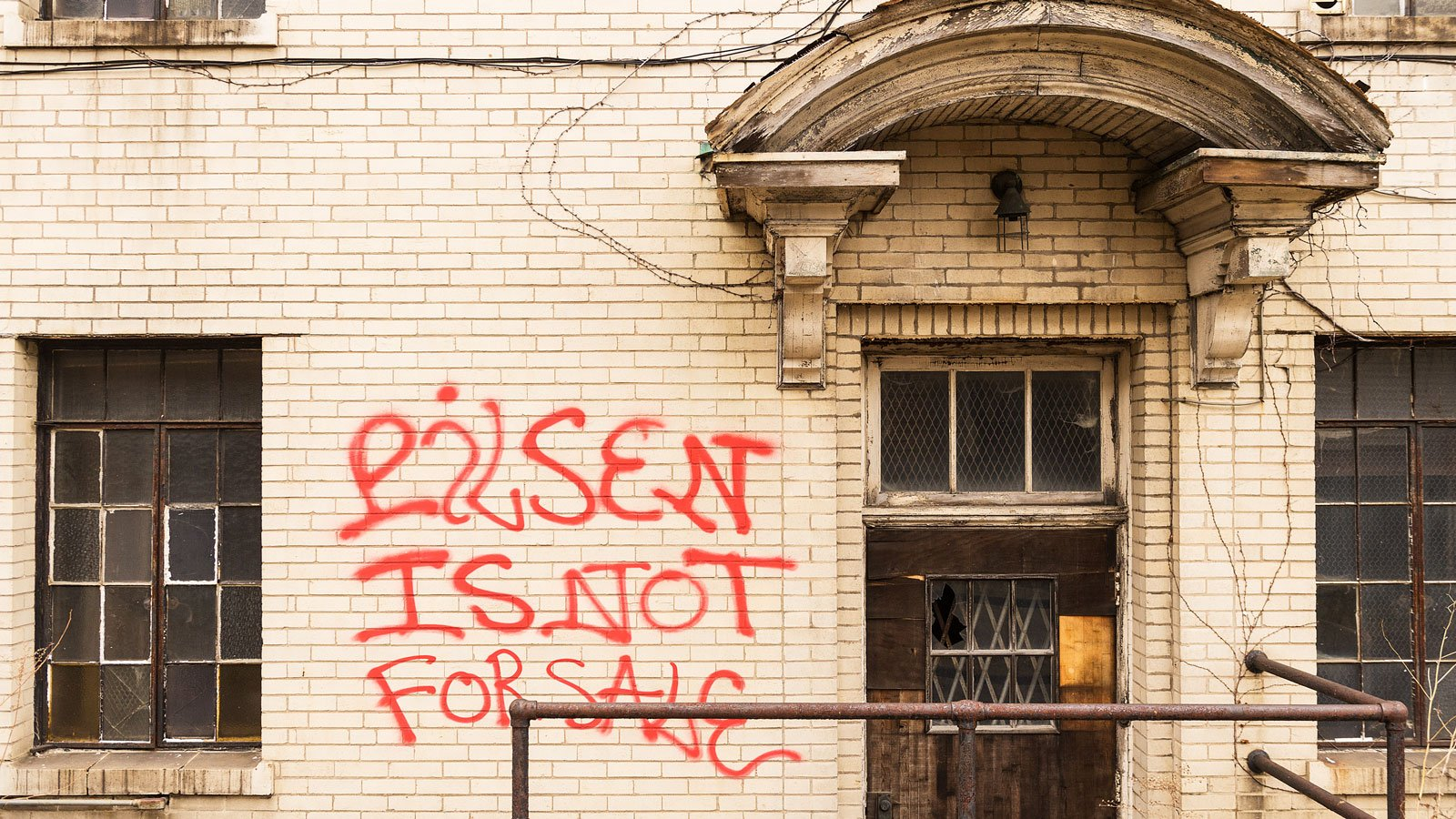 A dilapidated property is spray painted with a message, Pilsen Is Not For Sale.