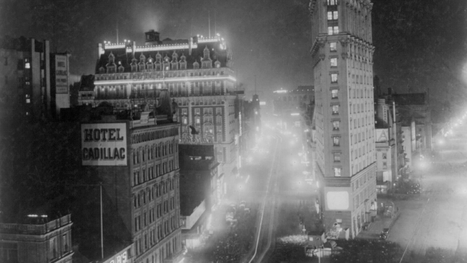 Broadway and West 42nd Street at night, with crowds gathered to see films projected outdoors, circa 1908