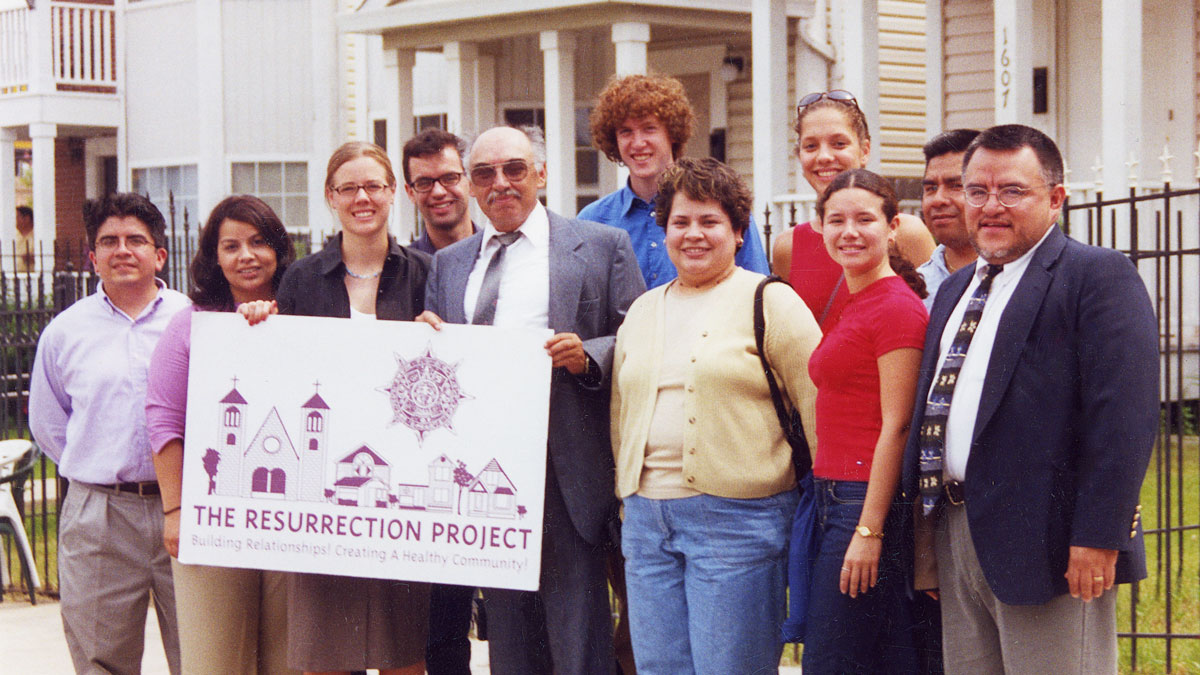 The Resurrection Project team stands in front of the new houses on Throop.