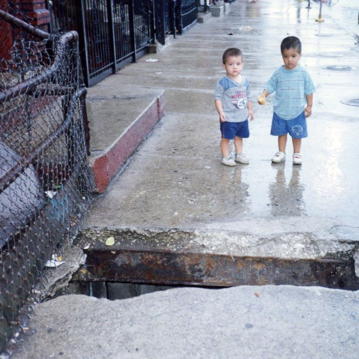 Two children by vaulted sidewalk with hole
