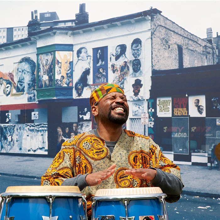 musician performing at the site of the 'Wall of Respect' in front of a photo of the mural