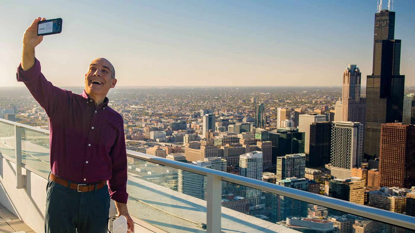 Geoffrey Baer taking selfie on skyscraper with Chicago skyline in background