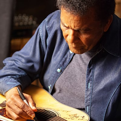 Charley Pride signs a Martin D-28 guitar. Pride is among the 76 of the 101 country music artists interviewed for the series who signed two Martin D-28 guitars. Photo: Courtesy of Craig Mellish