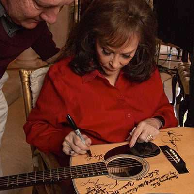 Loretta Lynn signs a Martin D-28 guitar. Photo: Courtesy of Jared Ames