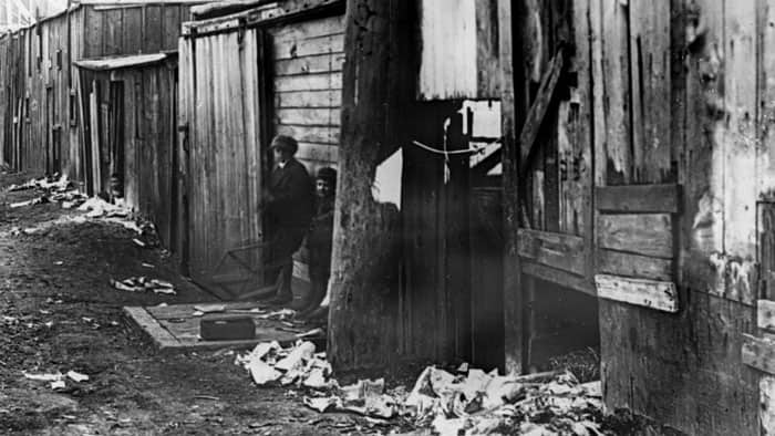 Children stand in a dirty alley between two rows of shanties