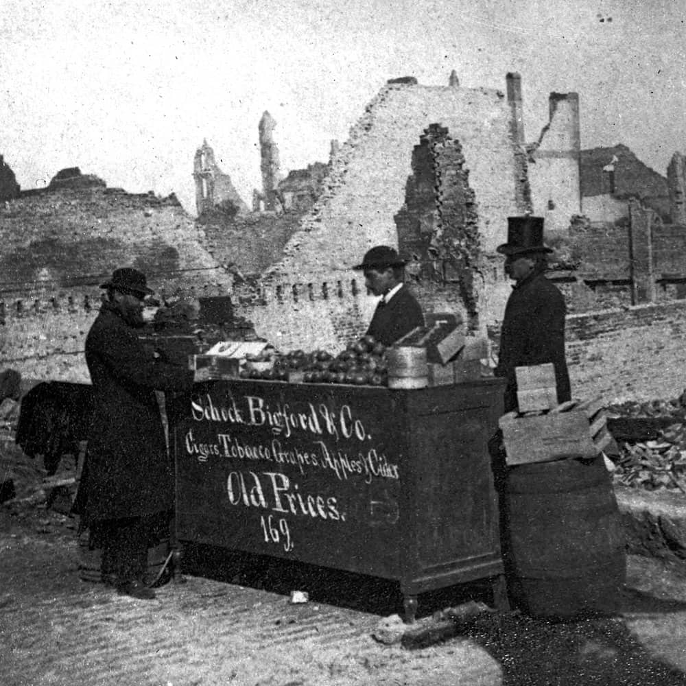 """Men work at a makeshift stand selling """"Cigars, Tobacco, Grapes, Apples & Cider"""" amid the ruins."""