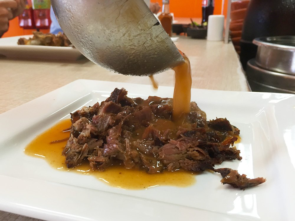 Ladling a consomme over the birria