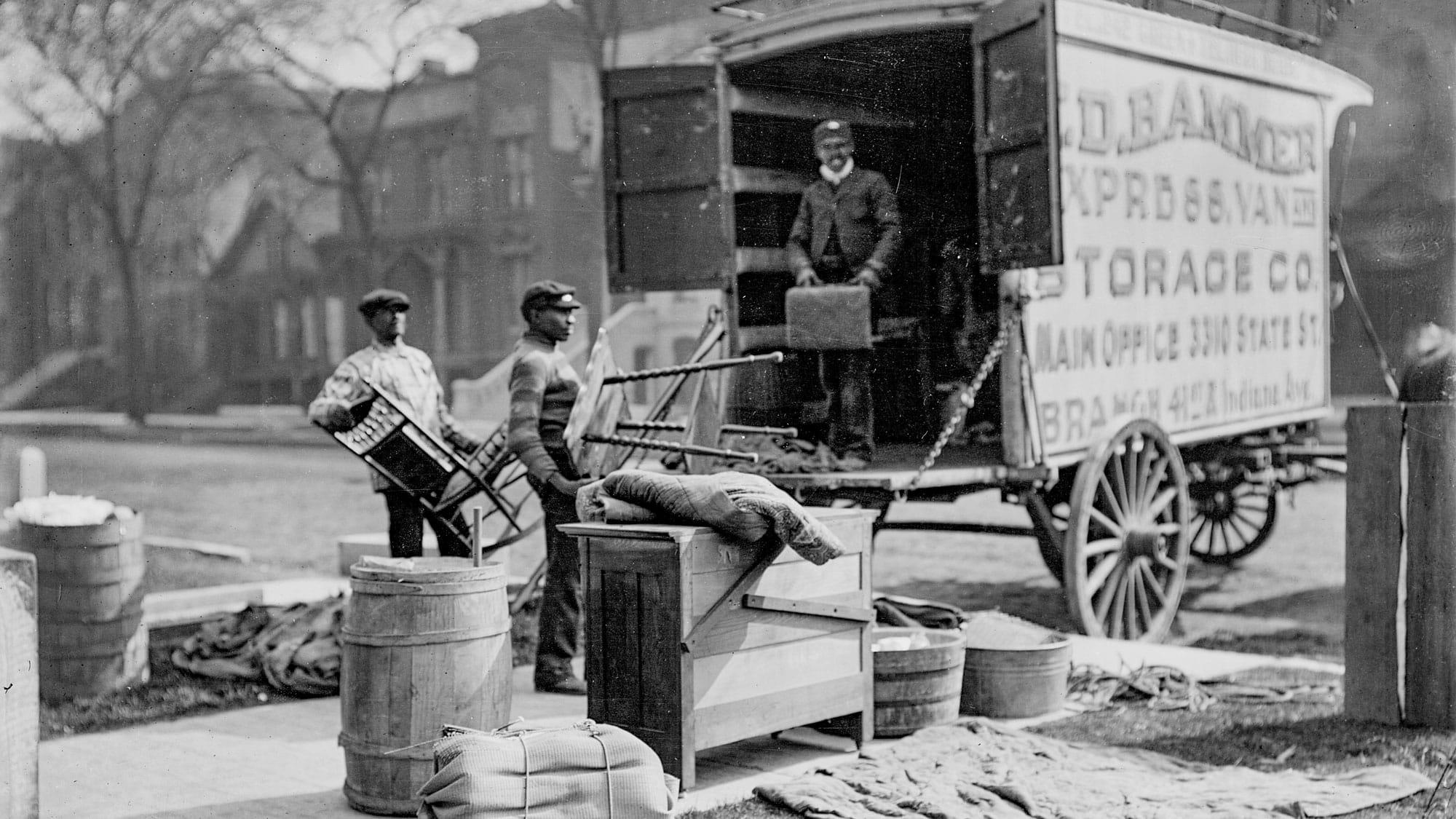 Black men loading goods on a horse-drawn moving van