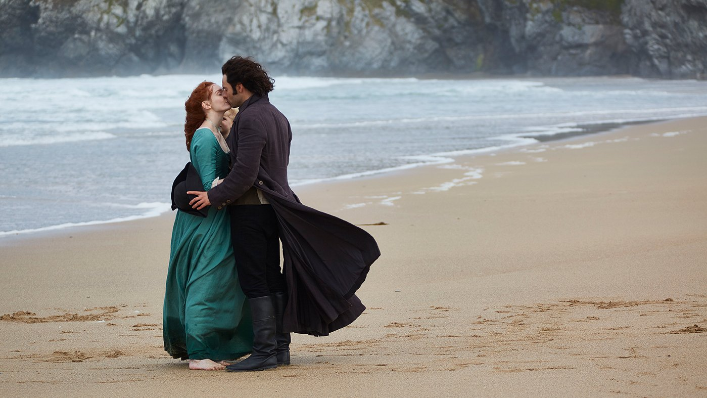 Eleanor Tomlinson as Demelza kisses Aidan Turner as Ross Poldark on the beach. Photo: Mammoth Screen for BBC and MASTERPIECE