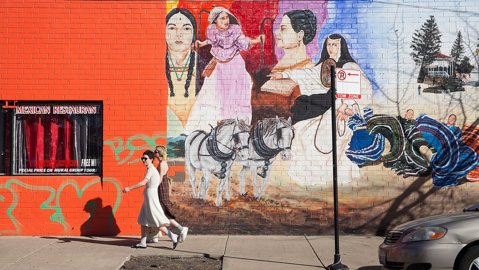 Two women walk along 18th street in Pilsen