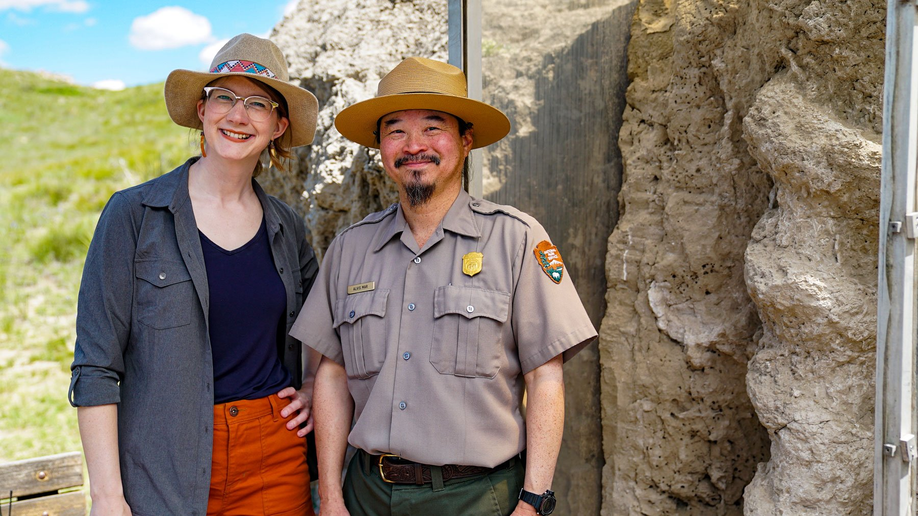 Emily Graslie and Agate Fossil Beds ranger Alvis Mar stand next to a fossil display of a daemonelix