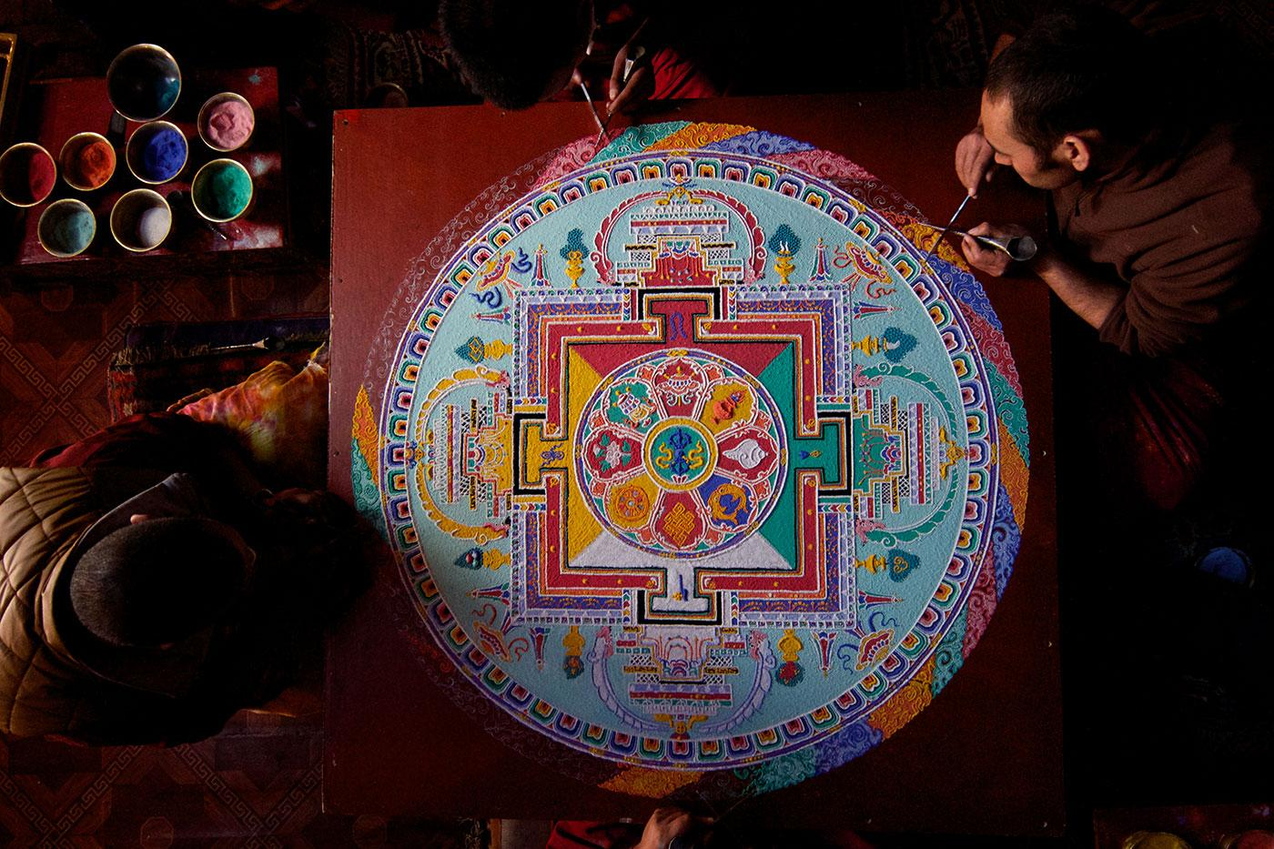 Buddhist monks at Phyang Monastery in Ladakh, India put the finishing touches on a sand Mandala. Photo: BBC/Anthony Pyper