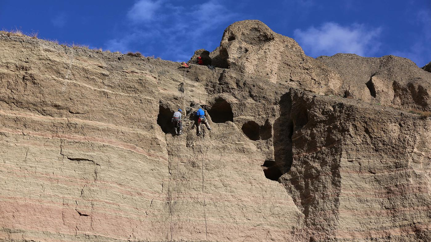 Climbers Pete Athans and Jake Norton excavating and photographing the Samdzong Sky Tombs, Upper Mustang, Nepal. Photo: Liesl Clark