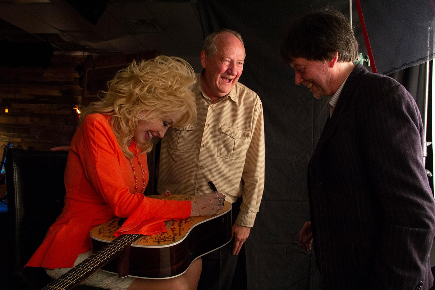Dolly Parton signs a Martin D-28 guitar, with Dayton Duncan and Ken Burns, after being interviewed for 'Country Music.' Photo: Katy Haas