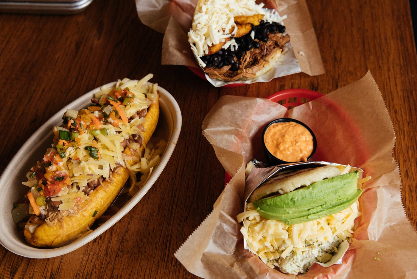 A stuffed plantain, pabellón arepa, and avocado chicken arepa with red pepper sauce at Sweet Pepper Venezuelan Food Bar. Photo: Sandy Noto for WTTW