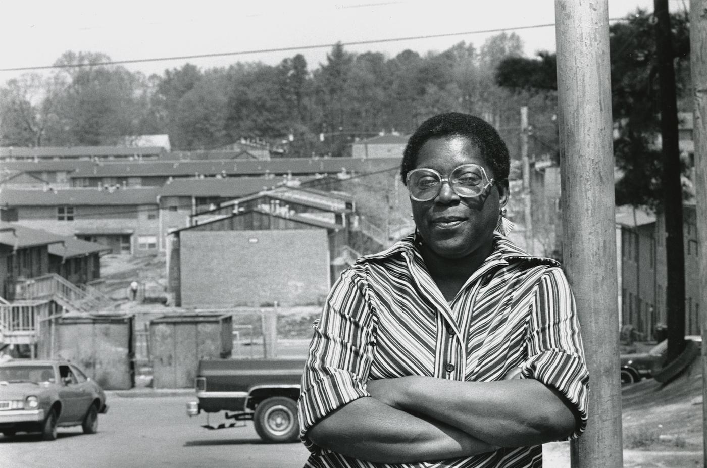 Eva Davis leans against a telephone pole, the buildings of of East Lake Meadows appear behind her. Atlanta, GA. September 8, 1986.