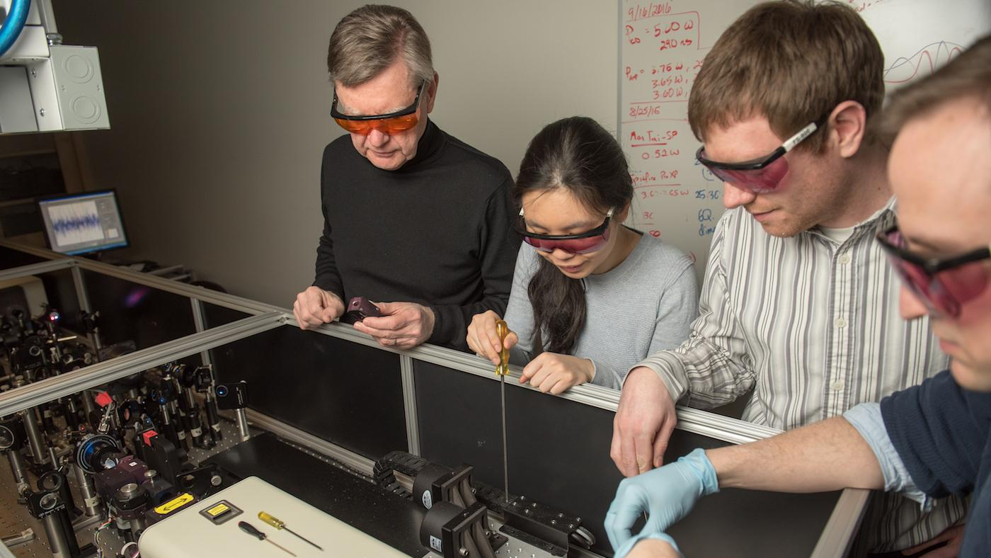 Northwestern Professor Michael R. Wasielewski works with students to tune an ultrafast laser system used for solar energy research. Photo: Institute for Sustainability and Energy at Northwestern University