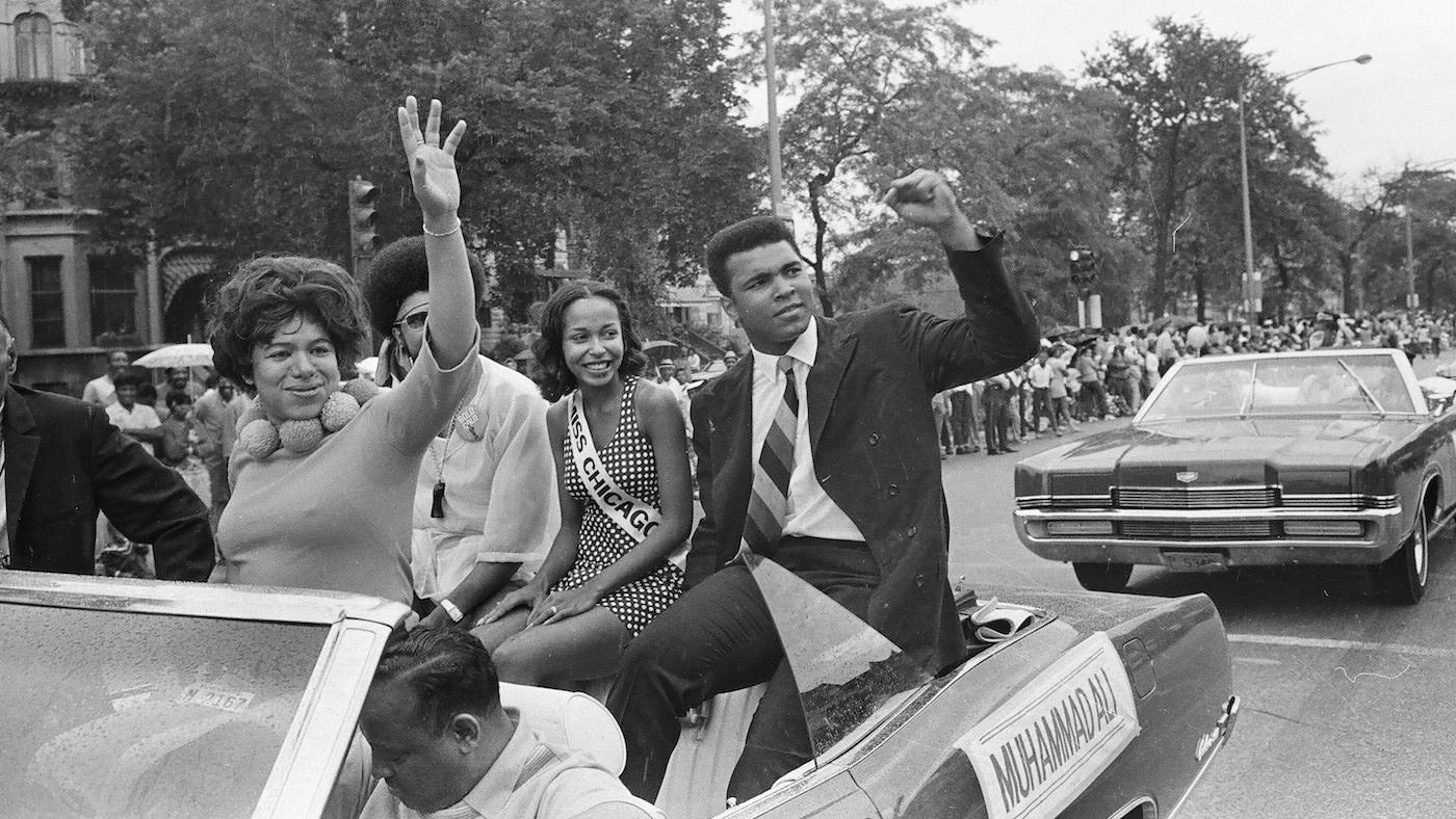 Muhammad Ali sitting in the back of a convertible waving to a crowd during the Bud Billiken Day Parade at 39th Street and Martin Luther King Drive, Chicago, Illinois on August 9, 1969. Photo: ST-40001287-0032, Chicago Sun-Times collection, Chicago History Museum
