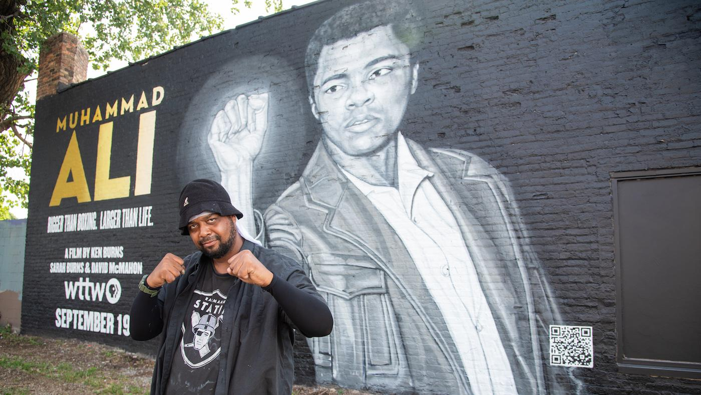 Rahmaan Statik in front of his Muhammad Ali mural. Photo: WTTW/Liz Markel