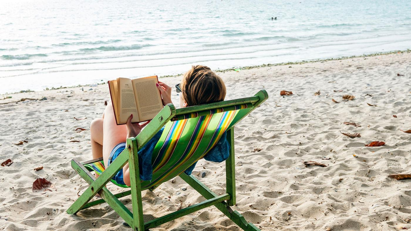 Summer reading on the beach. Photo: rawpixel on Unsplash