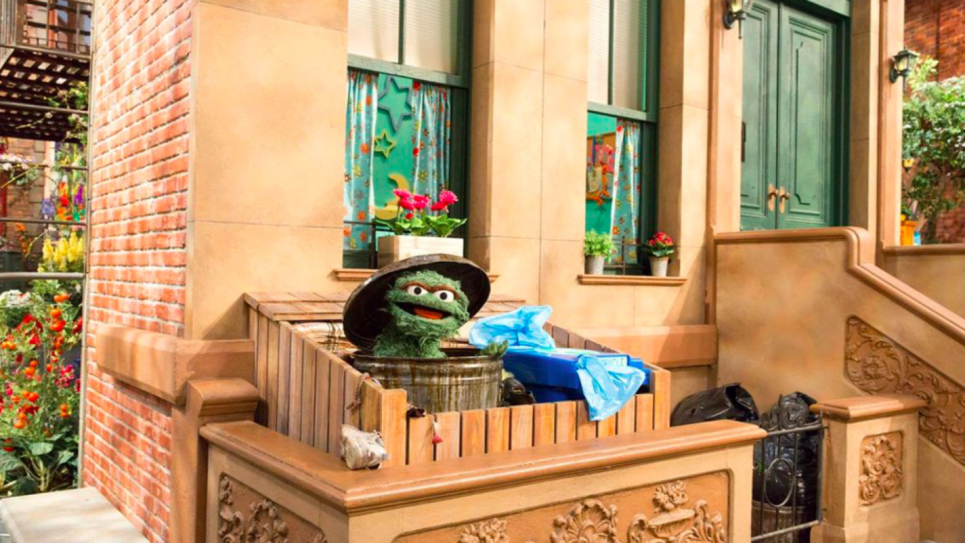 Oscar the Grouch by a recycling bin. Photo: Sesame Workshop