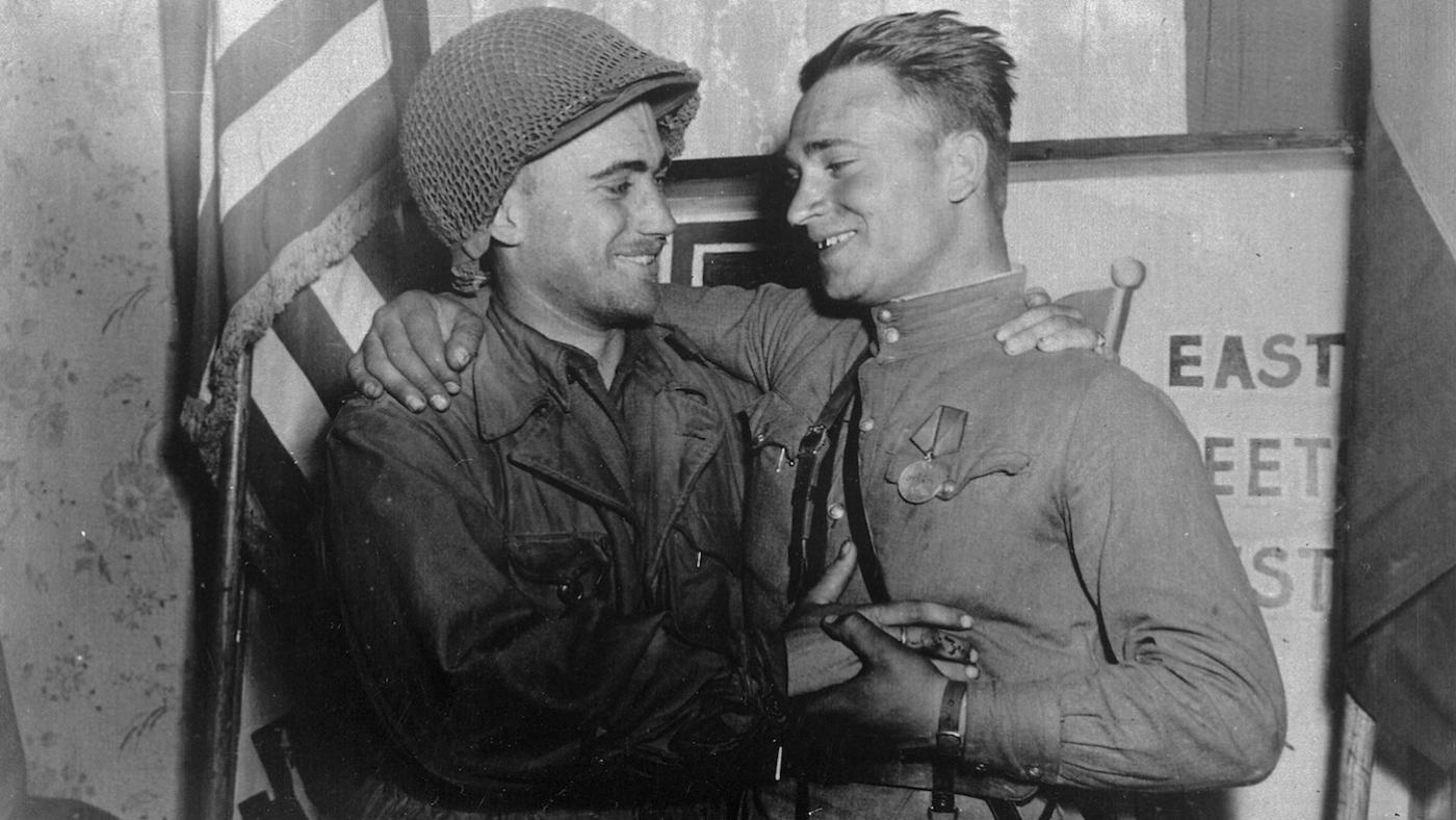 2nd Lt. William Robertson and Lt. Alexander Sylvashko, Red Army, shown in front of sign [East Meets West] symbolizing the historic meeting of the Soviet and American Armies, near Torgau, Germany on Elbe Day. Photo: Pfc. William E. Poulson/U.S. National Archives and Records Administration