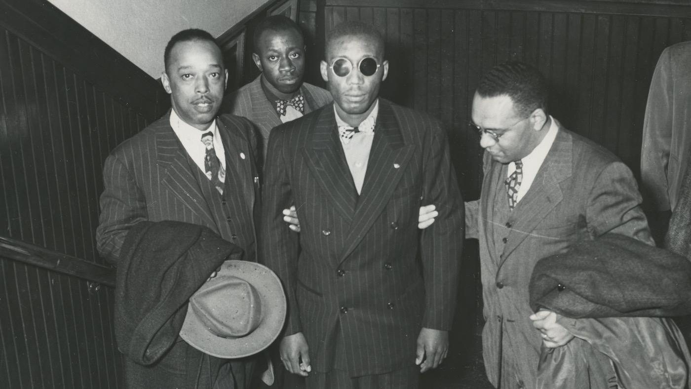 Leroy Carter, Isaac Woodard, and Donald Jones, NAACP assistant field secretary. Willie Mabry, Sgt. Woodard's cousin. in background. Likely taken while Woodard was on his speaking tour with the NAACP. 10/1946. Photo: AFRO American Newspapers Archives