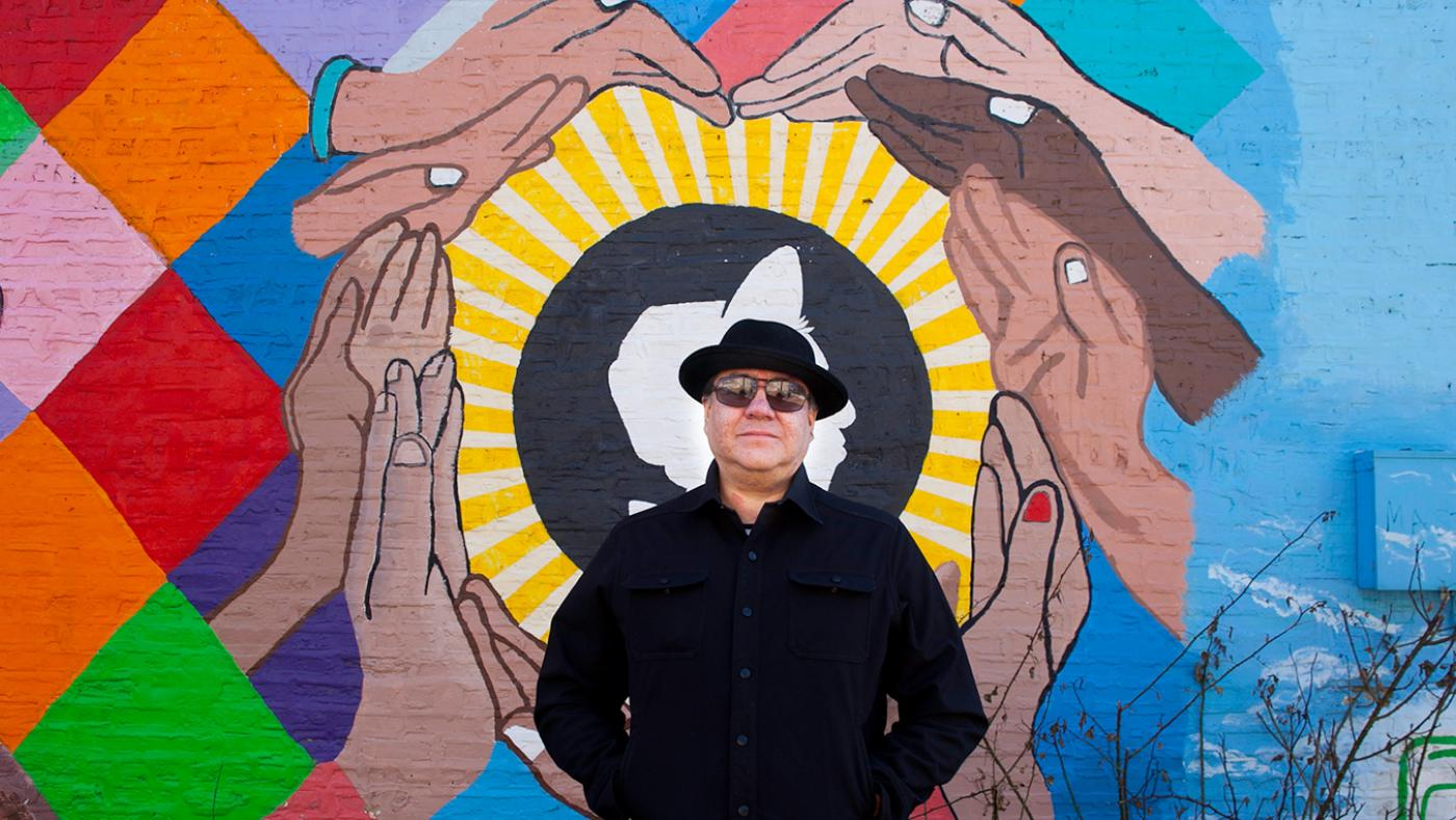 Jeff Maldonado stands in front of one of the many J-Def murals