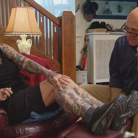 Helen Lambin shows Jay Shefsky her collection of tattoos