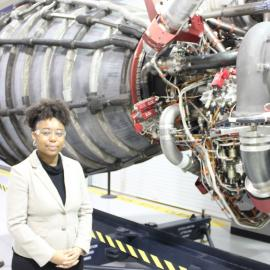 Advocate Tiera Fletcher by a rocket engine at NASA. Photo: Bigger Bang Communications