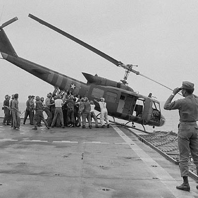U.S. Navy personnel push a helicopter into the sea to make room for more evacuation flights from Saigon. April 29, 1975. Photo: AP/Jacques Tonnaire