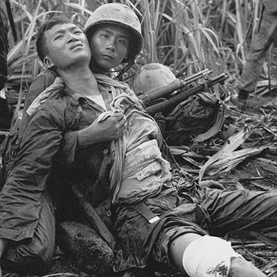 South Vietnamese soldier comforts severely wounded comrade. Near Saigon. August 5, 1963. Photo: AP/Horst Faas